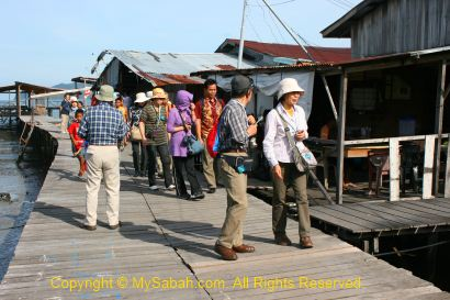 Tourists visit stilt houses