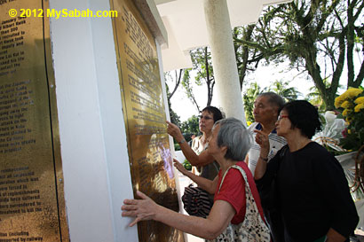 relatives looking for the name on plaque of Petagas war monument