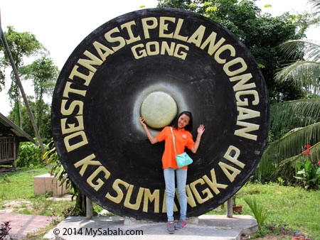 tourist taking picture with gong