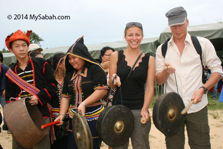 tourists beating gong