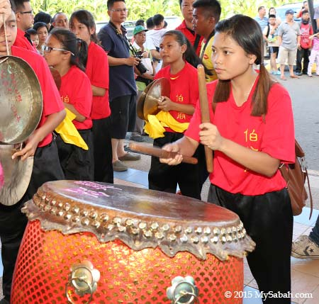 girl beating drum for lion dance