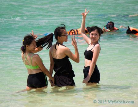 girls taking photo in water