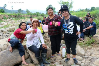 Enjoying drink with the villagers at the river side