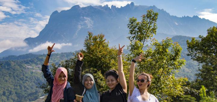 Four girls taking group photo with Mount Kinabalu