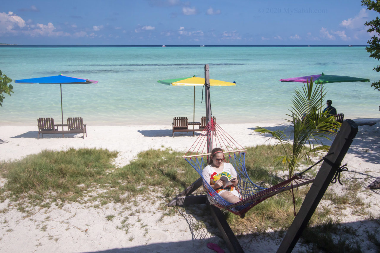 Reading book on the hammock of Timba-Timba Island
